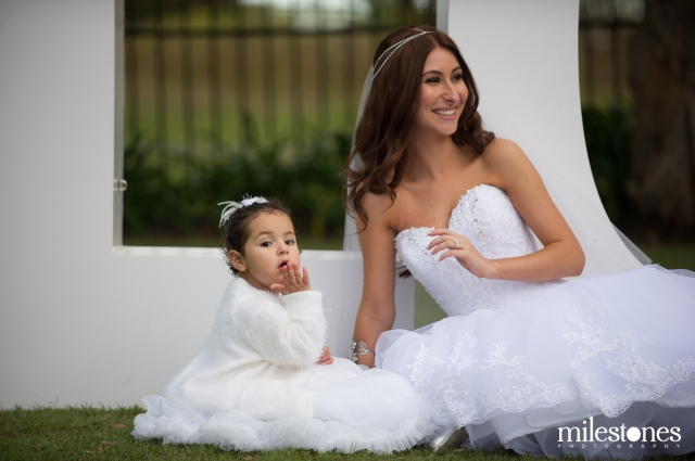 Bride and flower girl sitting on grass