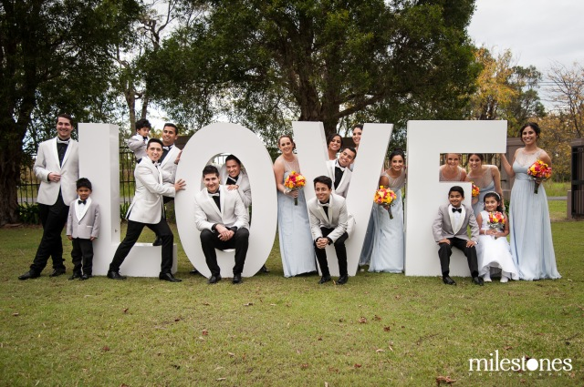 Bridal party sitting in Love sign